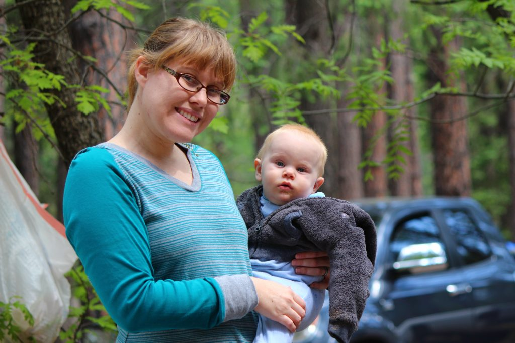 Mommy and baby posing at campsite in pine forest.