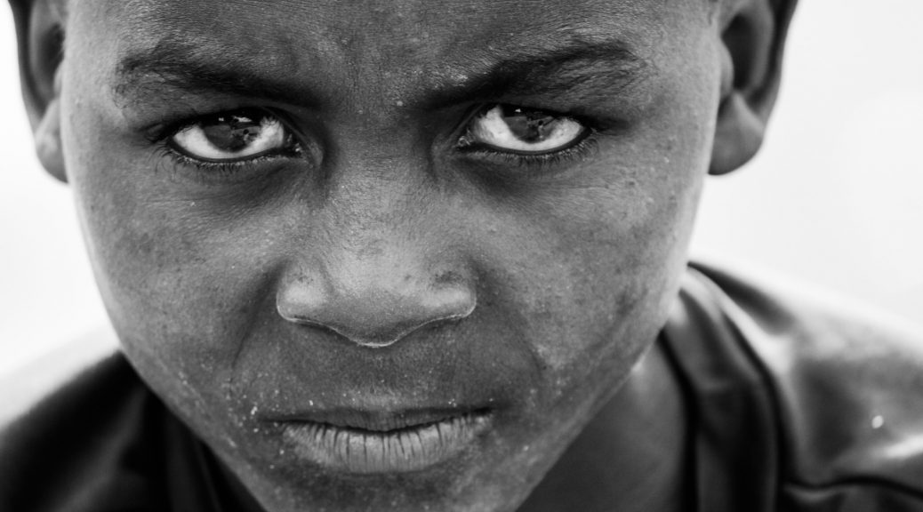 Close up of an African-American boy looking intensely into the camera.